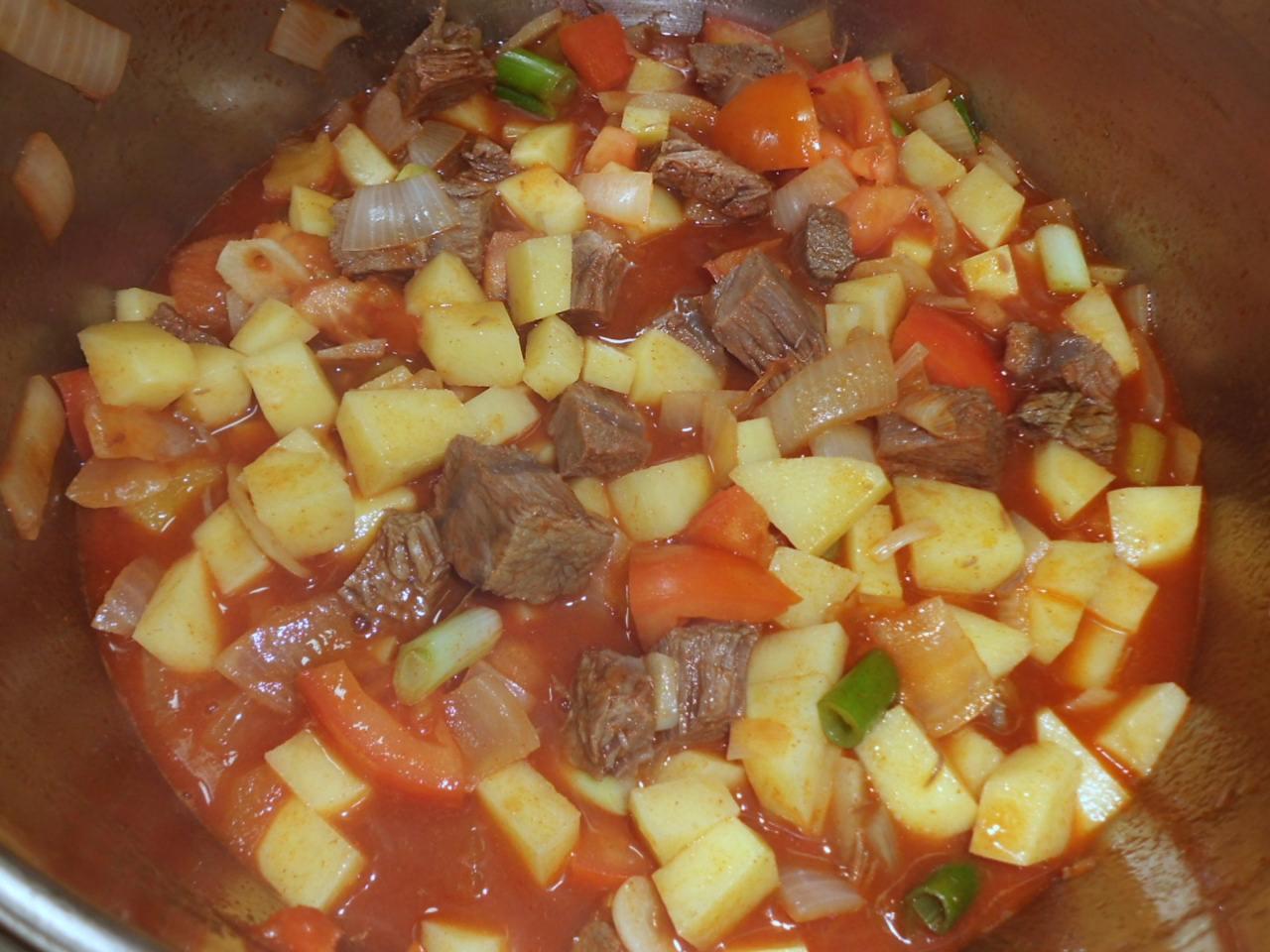 ablöschen mit Brühe und Kartoffel, Paprika,Tomaten und  Rindfleisch gar kochen