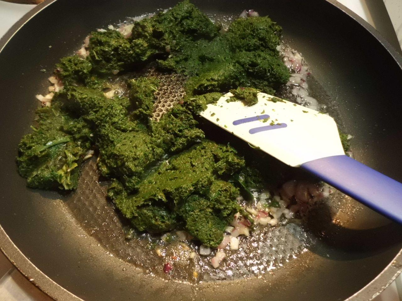 In die Pfanne den Spinat geben und unter Zwiebeln und Knoblauch rühren