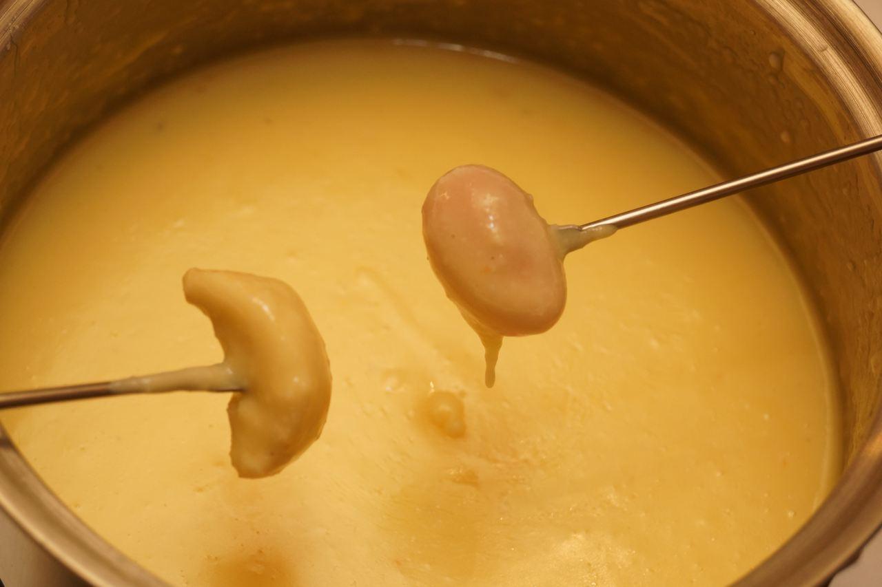 Brotwürfel und Kirschtomate ins Fondue getaucht