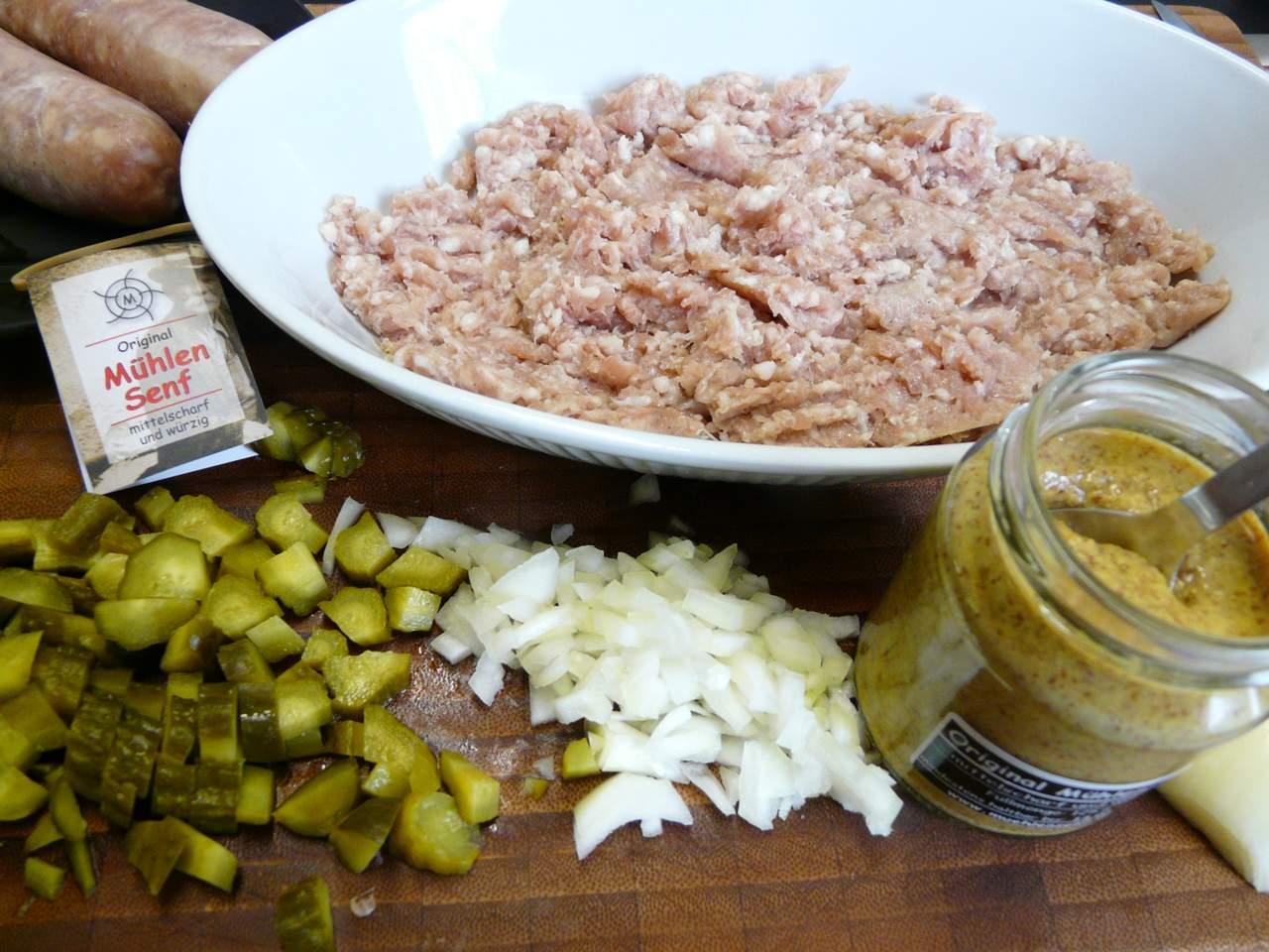 Frische grobe Bratwurst mit Zwiebeln, Gurken und Senf