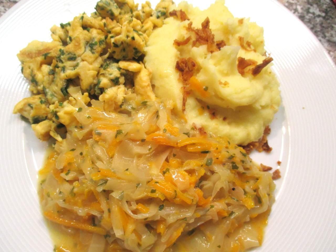 Angerichtet Kartoffelbrei mit gerösteten Zwiebeln, Rührei und Karotten-Weißkohl Gemüse