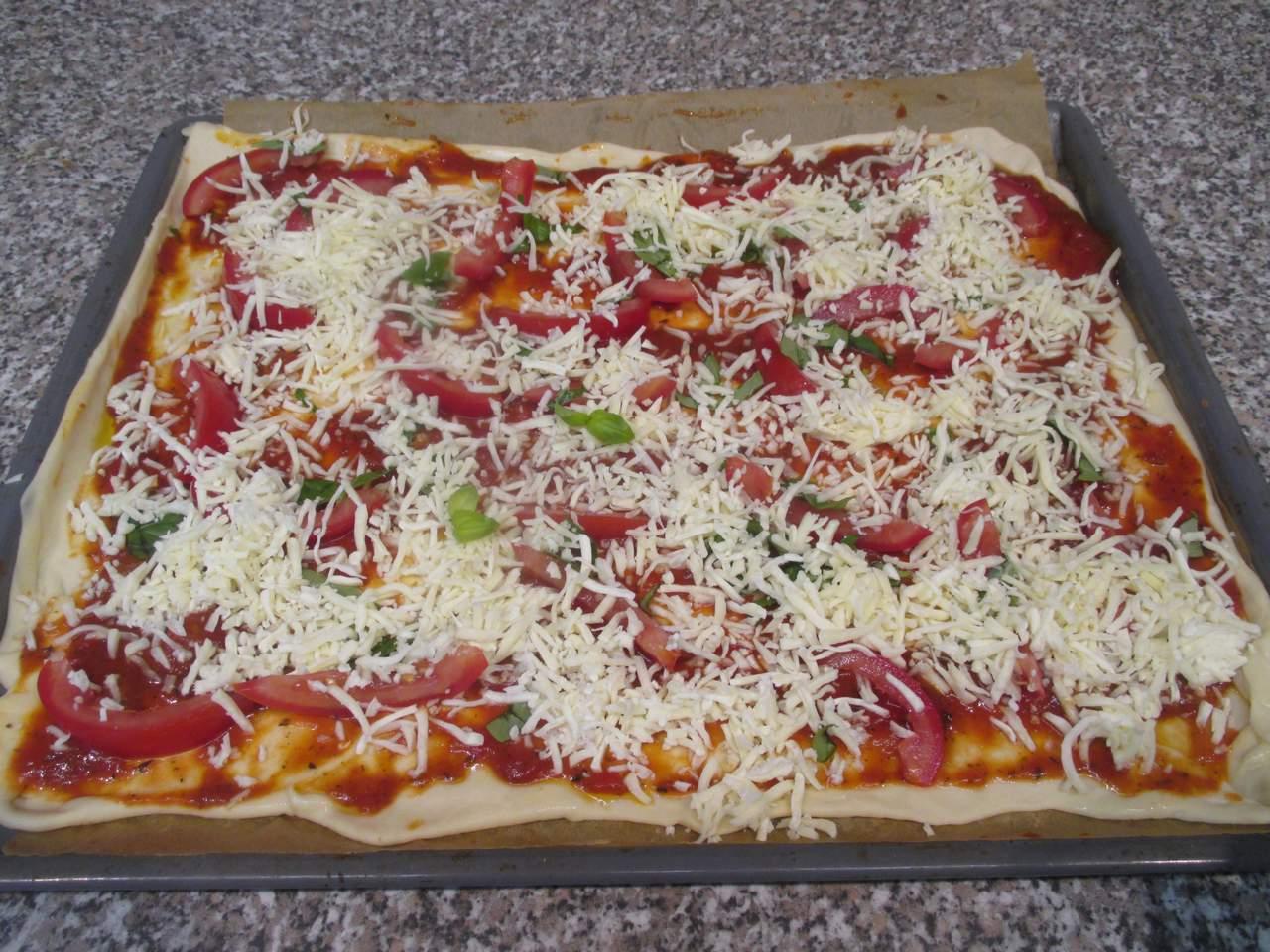 mit Tomaten, Basilikum und Mozzarella Käse bestreuen
