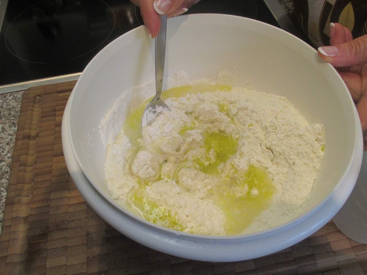 Nachden der Vorteig 15 Minuten gegangen ist die Flüssigkeit mit Olivenöl anrühren und weiter zu einem geschmeidigen Teig kneten