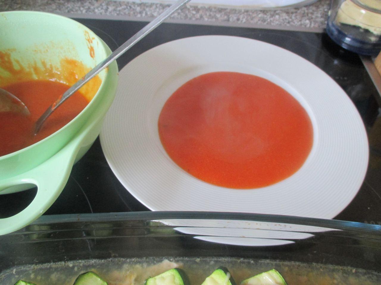 Auf einen heißen Teller ein Spiegel mit der Zucchini-Tomatensauce machen und darauf die Zucchinis legen und garnieren